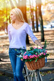 Woman on bicycle with flowers basket summer park outdoor. Stock Photo