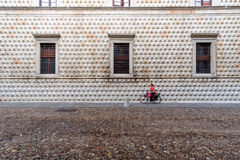 Woman on bicycle in front of the famous Palazzo dei Diamanti Stock Images