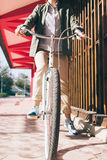 Woman on a bicycle in a green shirt and beige pants in the city. Vertical image Stock Photography