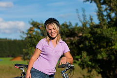Woman with bicycle and helmet. On a beautiful summer day stock photography