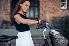 Woman with a bicycle looking at time on wristwatch Stock Image