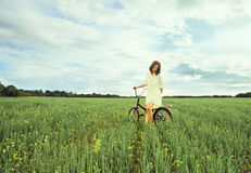 Woman with bicycle in the meadow Stock Image