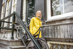 Woman with bicycle near the house entrance Royalty Free Stock Photo