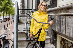Woman with bicycle near the house entrance Stock Photography