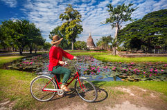 Woman with bicycle near temple in Thailand stock photography