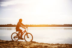 Woman on a bicycle near the water Royalty Free Stock Photos