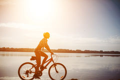 Woman on a bicycle near the water Royalty Free Stock Photo