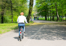 Woman on bicycle at park Stock Photo