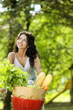 Woman on bicycle. Portrait of a beautiful young woman riding bicycle with groceries in basket stock image