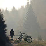 Woman with bicycle  resting on a bench Royalty Free Stock Images