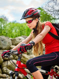 Woman on bicycle ride mountain. Girl traveling in summer park. Royalty Free Stock Photo