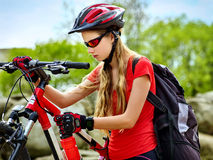 Woman on bicycle ride mountain. Girl traveling in summer park. Early morning with blue sky and clouds. Cycling person with rucksack. Sport trip is good for Stock Photography
