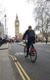 Woman with bicycle riding in central London city. Big Ben in background Stock Photos