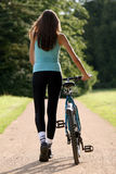 Woman with bicycle on the road Stock Photography