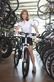 Woman With Bicycle In Shop Royalty Free Stock Photography