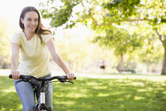 Woman on bicycle smiling stock images