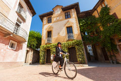 Woman on a bicycle through the streets of the country Stock Photos