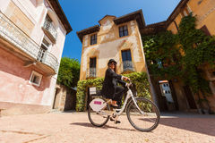 Woman on a bicycle through the streets of the country Royalty Free Stock Photo