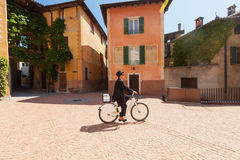 Woman on a bicycle through the streets of the country Stock Images