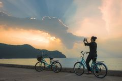 Woman on bicycle taking photo by smart phone of beautiful sun light beam over sky Stock Images