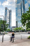 Woman on a bicycle with tall office buildings in the background Stock Photography