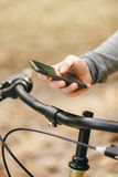 Woman with bicycle using mobile phone outdoors Royalty Free Stock Photos