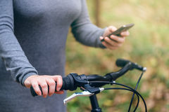 Woman with bicycle using mobile phone outdoors Royalty Free Stock Image