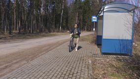Woman with bicycle walking near bus stop. In summer day stock video