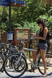 Woman bicyclist looking a map. Woman bicyclist searching on a map in centre of El Raval, Barcelona, june 2015 Stock Photography
