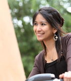 Woman on a bicykle outdoors smiling. Young woman on a bicykle outdoors smiling Stock Images