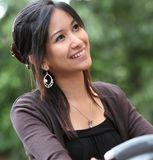 Woman on a bicykle outdoors smiling. Young woman on a bicykle outdoors smiling Royalty Free Stock Images