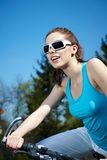Woman on a bicykle outdoors smiling Stock Images