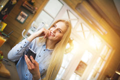 Woman with big blue eyes with phone in hand dreaming about something in the cafe decorated for New Year holidays. Beautiful young woman with big blue eyes with Royalty Free Stock Photos