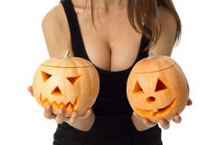 Woman with big boobs in halloween style. Close up of woman with big boobs in halloween style with two pumpkins in hands looking at camera in studio isolated on stock photos