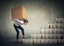Woman with big box on her back climbing up a stair made of jars with women inside Royalty Free Stock Photos