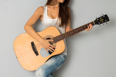 Woman with big breast and guitar in hands. Closeup of young sexy woman with big breast and guitar in hands in studio Royalty Free Stock Photo