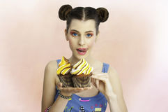 Woman with big cupcake cookies. Girl big blue eyes fashion model holding two big cup cakes with tong out of her mouth ready to taste it royalty free stock photo