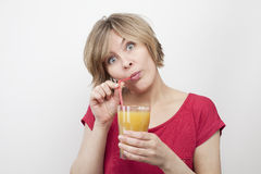 Woman with big eyes drinking juice with straw Royalty Free Stock Photo