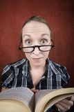 Woman with big eyes reading a book Royalty Free Stock Image