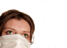 Woman with big green eyes wearing medical mask. Protecting against flu virus Royalty Free Stock Photos
