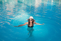 Woman in big hat relaxing on the swimming pool Stock Photography