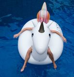 Woman with big inflatable unicorn in the pool. Top view of woman`s hands and legs laying down on the big white inflatable unicorn in the pool Royalty Free Stock Photo
