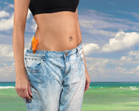 Woman with big jeans weight loss. Beautiful young woman with big jeans, isolated on white.Woman showing how much weight she lost. Healthy lifestyles concept Royalty Free Stock Photo