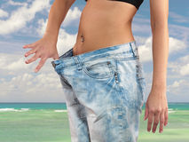 Woman with big jeans weight loss. Beautiful young woman with big jeans, isolated on white.Woman showing how much weight she lost. Healthy lifestyles concept Stock Photography