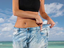 Woman with big jeans weight loss. Beautiful young woman with big jeans, isolated on white.Woman showing how much weight she lost. Healthy lifestyles concept Stock Photos