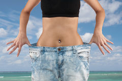 Woman with big jeans weight loss Royalty Free Stock Photos