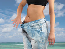 Woman with big jeans weight loss. Beautiful young woman with big jeans, isolated on white.Woman showing how much weight she lost. Healthy lifestyles concept Stock Images