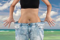 Woman with big jeans weight loss. Beautiful young woman with big jeans, isolated on white.Woman showing how much weight she lost. Healthy lifestyles concept Stock Photo