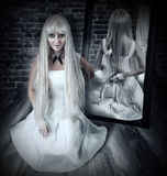 Woman with big knife in mirror reflection. Young beautiful blond woman sitting on wooden floor in old dark room with big knife in mirror reflection stock image