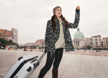 Woman with big luggage bag handwaving to someone, Venice Royalty Free Stock Images